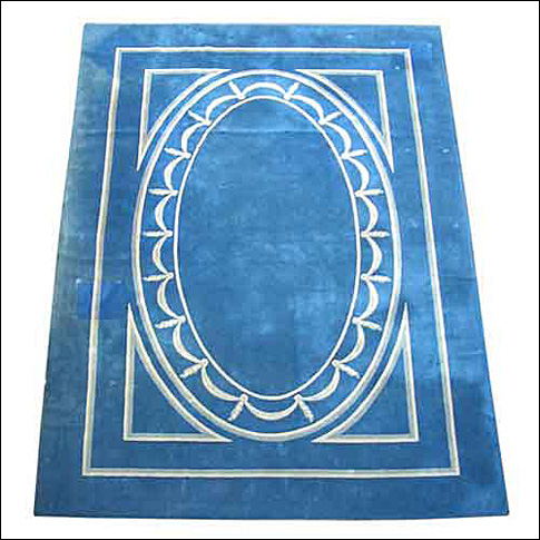 A custom made wool carpet with draped garland en grisaille border against a blue background by American maker V'Soske.